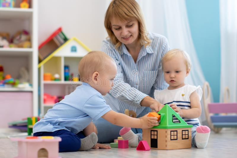 Cute babies play with carer in nursery or kindergarten royalty free stock images