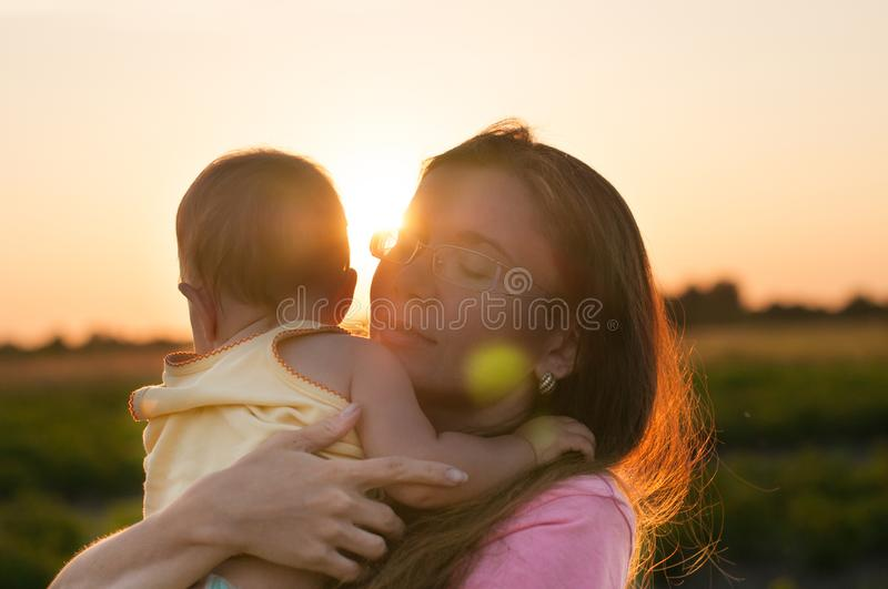 Cute baby in the arms of a happy mother in the rays of the setting sun. The concept of a good family. royalty free stock image