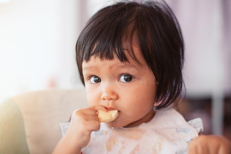 Cute baby asian child girl eating healthy food by herself stock photos