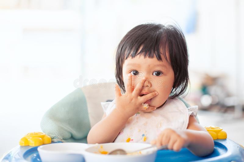 Cute baby asian child girl eating healthy food by herself stock photo