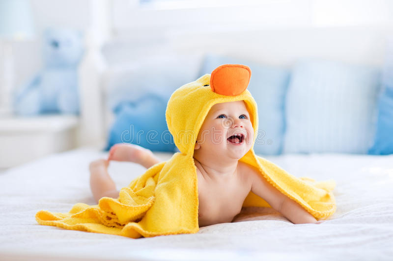 Cute baby after bath in yellow duck towel stock image