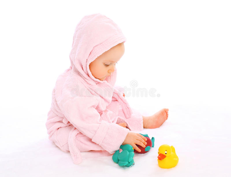 Cute baby in bathrobe playing with water toys. Cute baby in bathrobe playing with water rubber toys royalty free stock photography