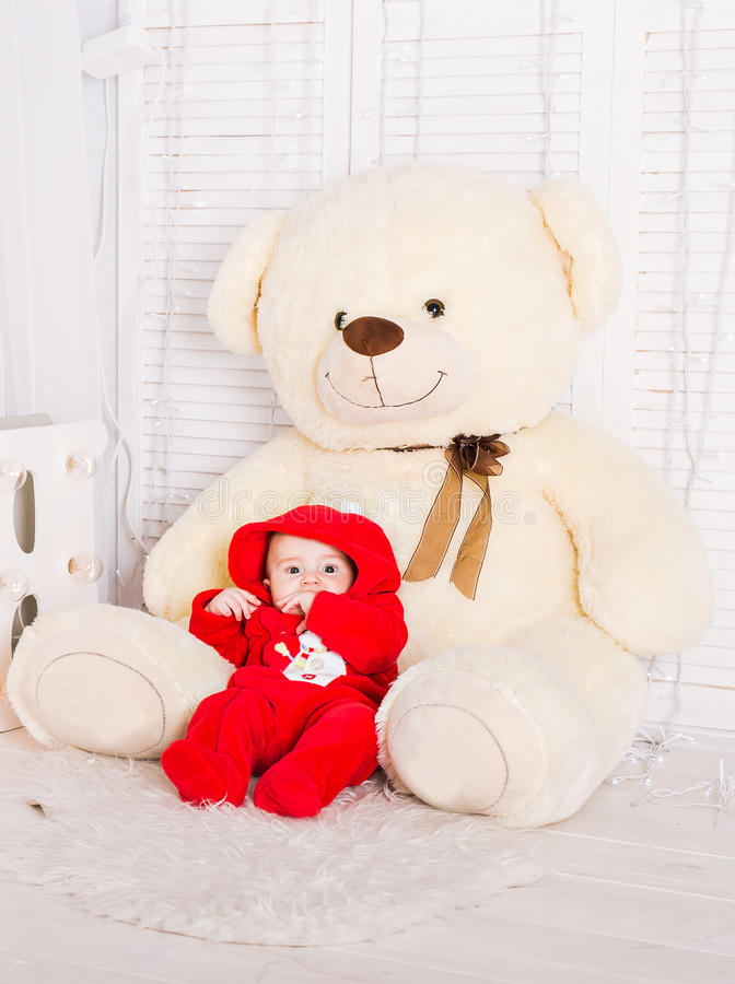 Cute baby with big teddy bear on white room.  royalty free stock photo