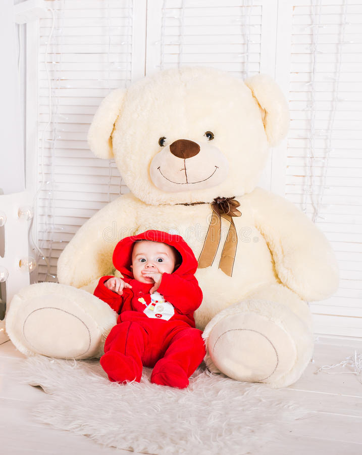 Cute baby with big teddy bear on white room.  royalty free stock images