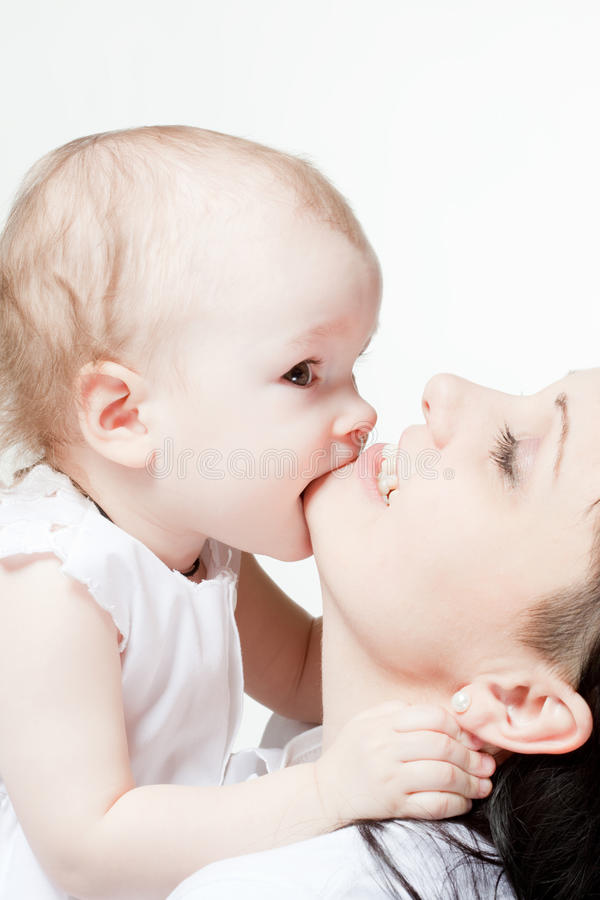 Cute baby biting her mother's chin. Closeup portrait stock image