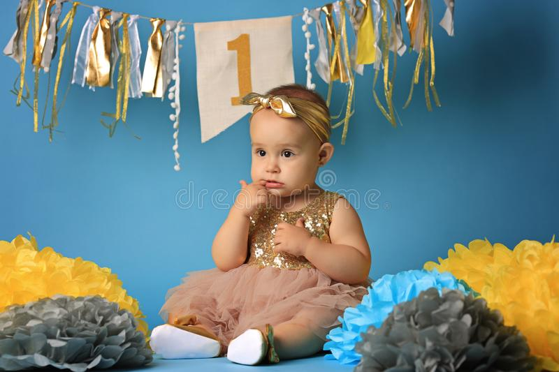 Cute baby on blue background.Close up headshot of a caucasian baby girl, 12 months old baby looking at camera. royalty free stock image
