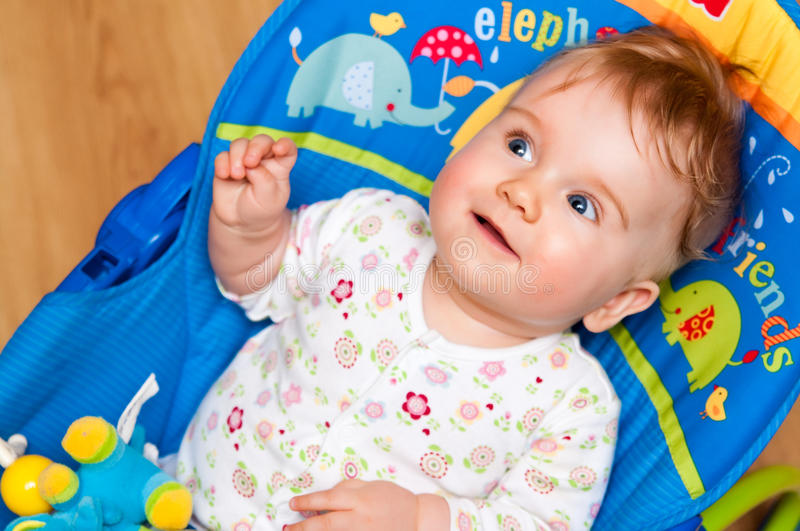 Cute baby on bouncy chair royalty free stock image