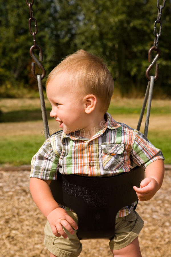 Cute Baby Boy. A portrait of a cute one year old baby boy on a swing royalty free stock photo