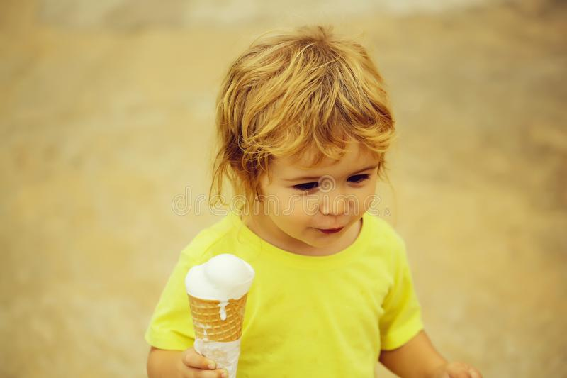Cute baby boy child. With curly blond curly hair in yellow shirt with ice cream outdoor on blurred background royalty free stock photography