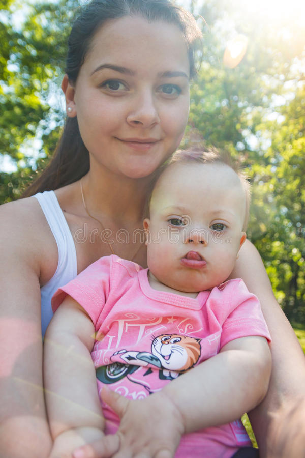 Cute baby boy with Down syndrome and his young mother in summer day royalty free stock image