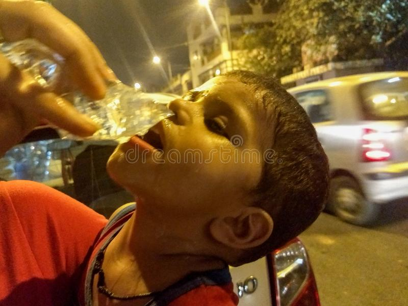 Cute baby boy drinking water during hot summer in Delhi India stock images