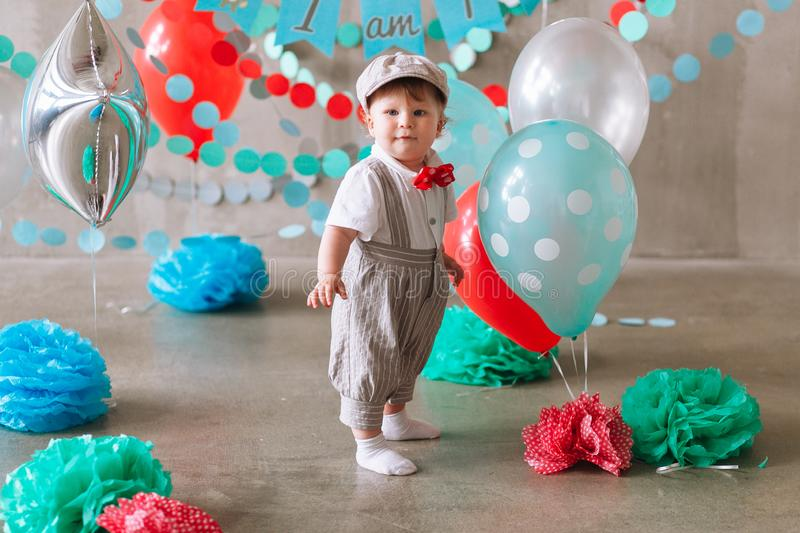 Cute baby boy first birthday party decorated with garland and balloons. Minimal studio photo.  royalty free stock photos