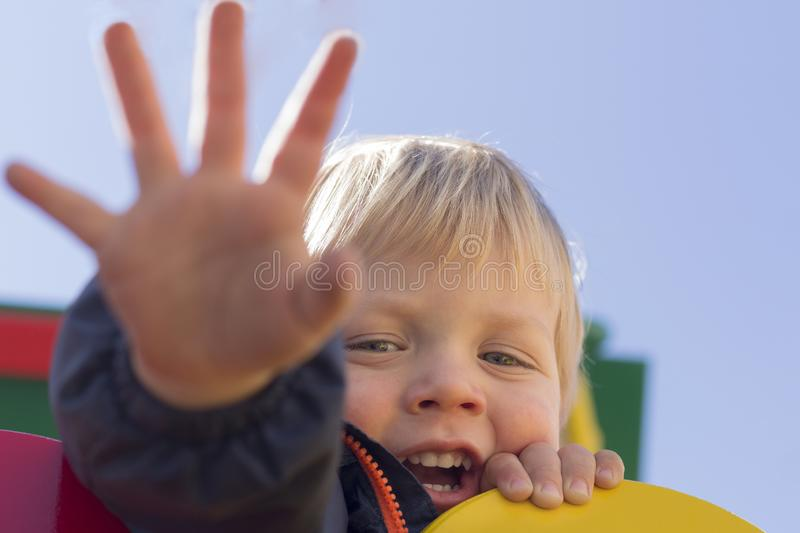 Cute baby boy giving high five to someone. Happy smiling portrait of child, outside. Close-up of adorable kid enjoying royalty free stock photos