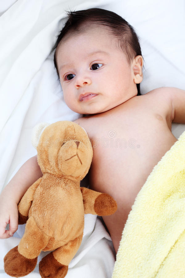 The cute baby boy is happy with yellow blanket and doll bear lovely friend on the white bed royalty free stock images