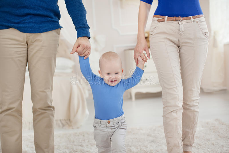 Cute baby boy holding father and mother by the hand and takes first steps royalty free stock image