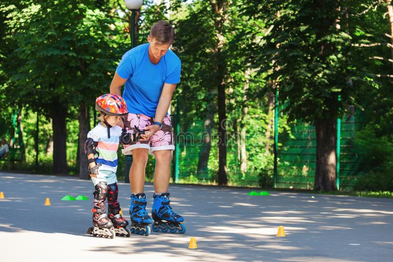 Cute baby boy with inline skating instructor in the park learining to skate. royalty free stock image