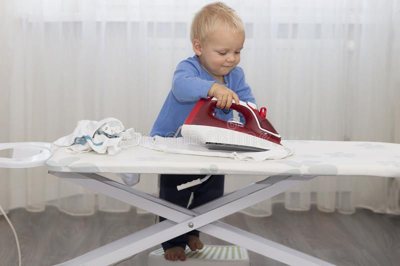 Cute baby boy with iron. Funny toddler ironing clothes royalty free stock images