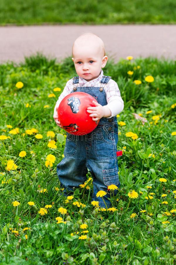 Cute baby boy on a lawn with the ball royalty free stock images