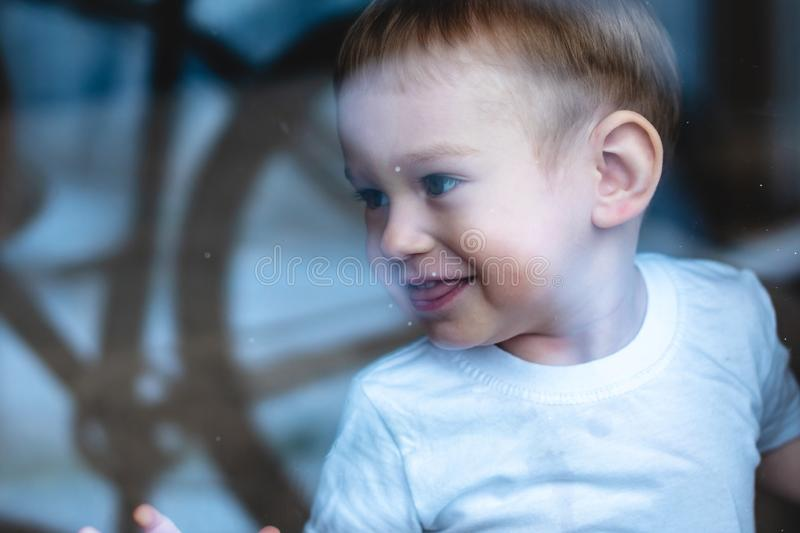 Cute baby boy looking in the window glass with reflection. Loneliness of children. Orphanage and orphans. Cute baby boy looking in the window glass with royalty free stock image