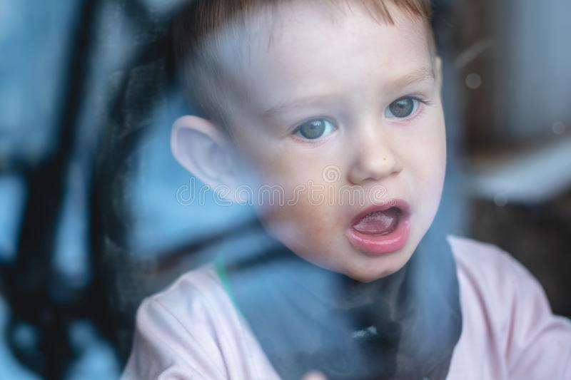 Cute baby boy looking in the window glass with reflection. Loneliness of children and waiting for kindness. Beautiful cute baby boy looking in the window glass stock photos