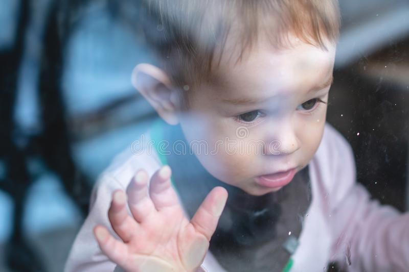 Cute baby boy looking in the window glass with reflection. Loneliness of children and waiting for kindness. Beautiful cute baby boy looking in the window glass royalty free stock photo