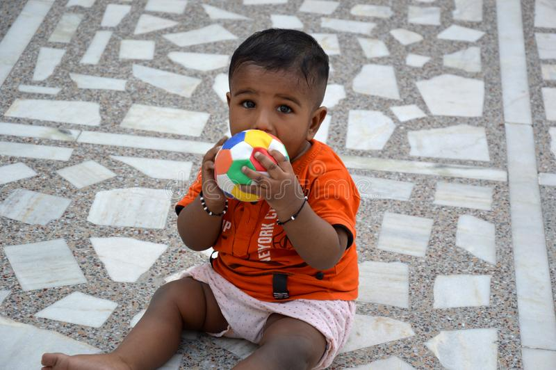 A cute baby boy playing with ball. stock photos