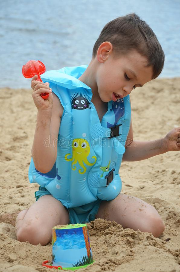 Cute baby boy playing with beach toys stock photo
