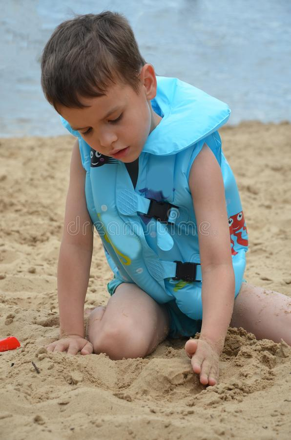 Cute baby boy playing with beach toys stock image
