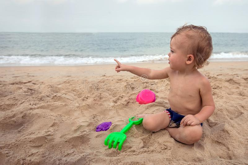 Cute baby boy playing with beach toys royalty free stock photos