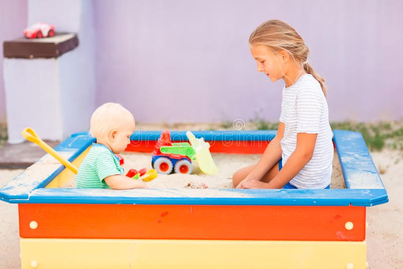 Cute baby boy playing with his sister in the sandbox. Cute baby boy playing with his sister with toys in the sandbox outdoor stock photo