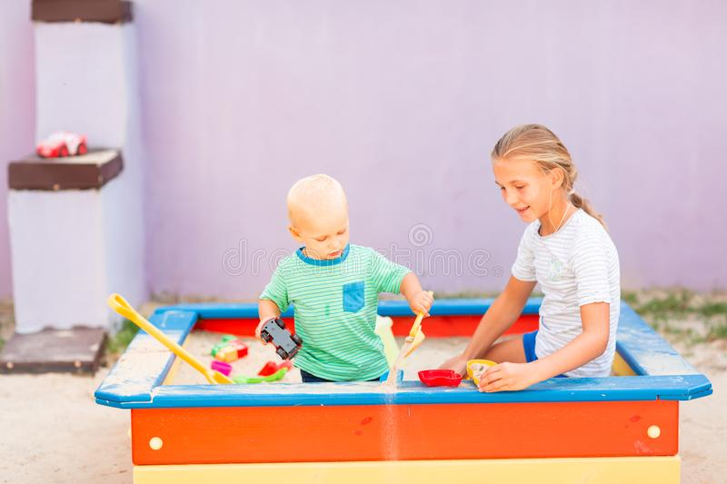 Cute baby boy playing with his sister in the sandbox. Cute baby boy playing with his sister with toys in the sandbox outdoor stock image