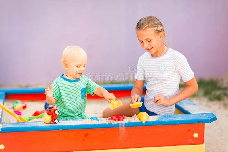 Cute baby boy playing with his sister in the sandbox. Cute baby boy playing with his sister with toys in the sandbox outdoor stock photos