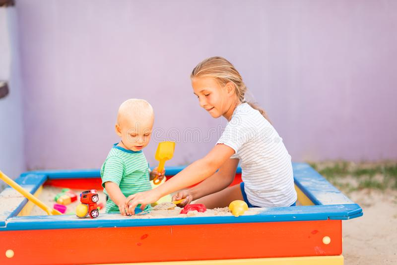 Cute baby boy playing with his sister in the sandbox. Cute baby boy playing with his sister with toys in the sandbox outdoor royalty free stock photo