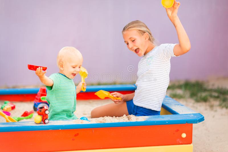 Cute baby boy playing with his sister in the sandbox. Cute baby boy playing with his sister with toys in the sandbox outdoor royalty free stock images
