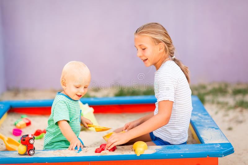 Cute baby boy playing with his sister in the sandbox. Cute baby boy playing with his sister with toys in the sandbox outdoor royalty free stock photography