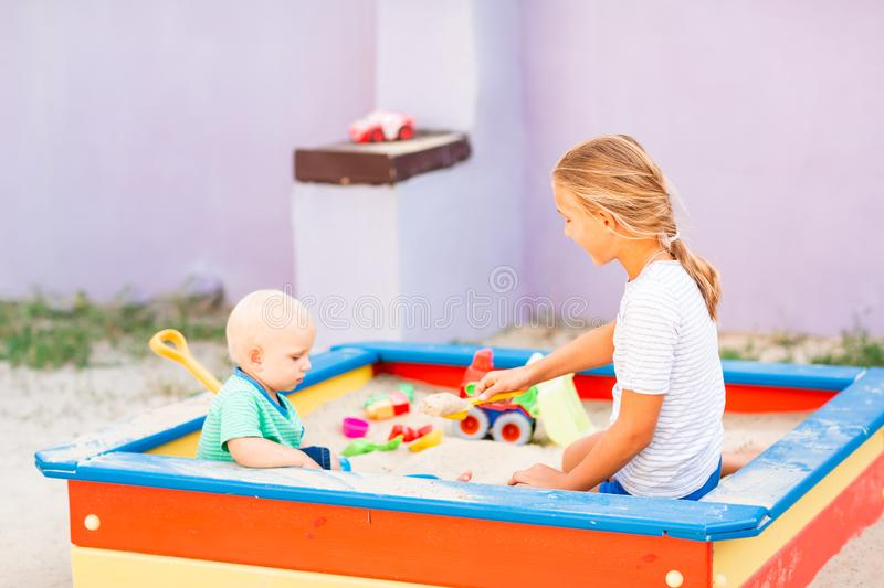 Cute baby boy playing with his sister in the sandbox. Cute baby boy playing with his sister with toys in the sandbox outdoor stock photography