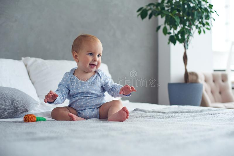 Cute baby boy playing with knitted toy on bed at home royalty free stock photos