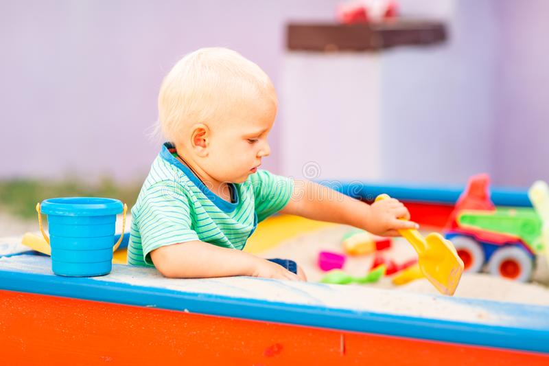 Cute baby boy playing in the sandbox royalty free stock image