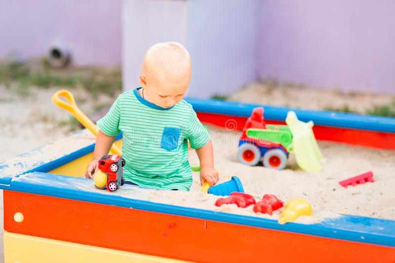 Cute baby boy playing in the sandbox stock image