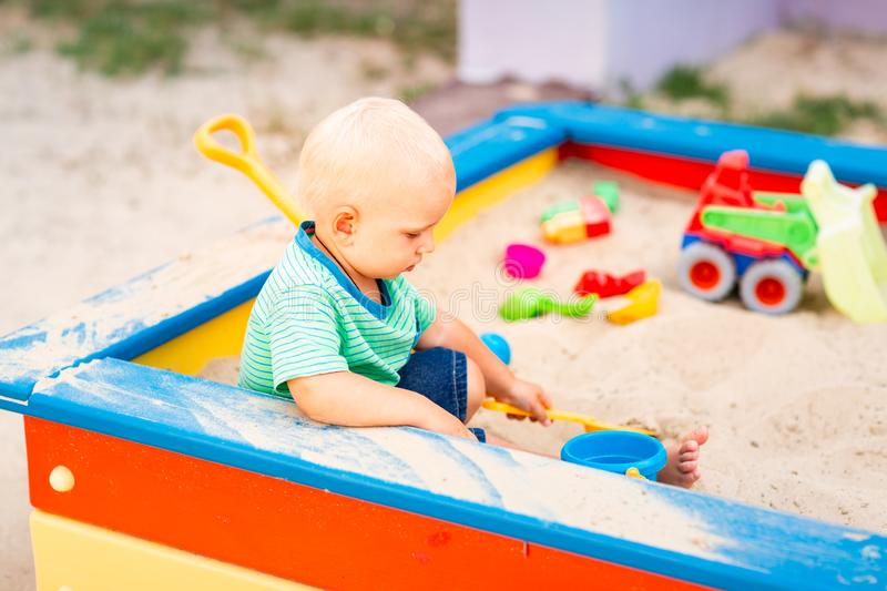 Cute baby boy playing in the sandbox stock photos
