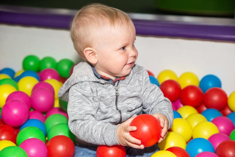 Cute baby boy plays with colorful balls in play ground. Ball pit poll at kids play center.  royalty free stock images