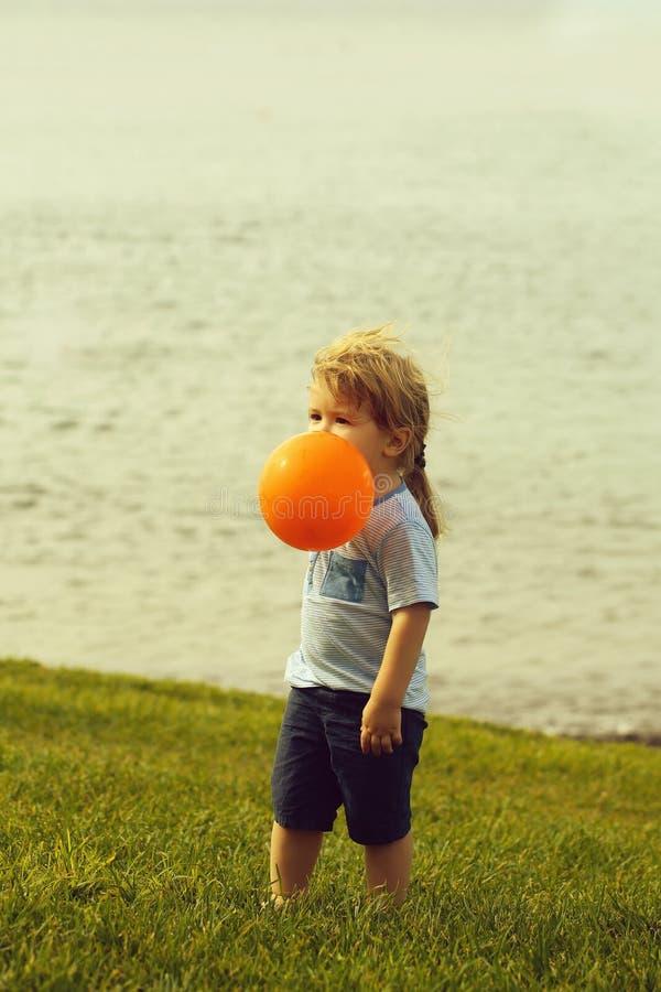 Cute baby boy plays with orange toy balloon stock photos