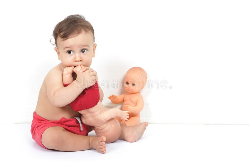 A cute baby boy plays with toys and tastes them royalty free stock photo