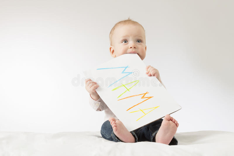 Cute baby boy with poster. Concept for postcard to Mothers day. Copy space. Colorful sign Mama royalty free stock images