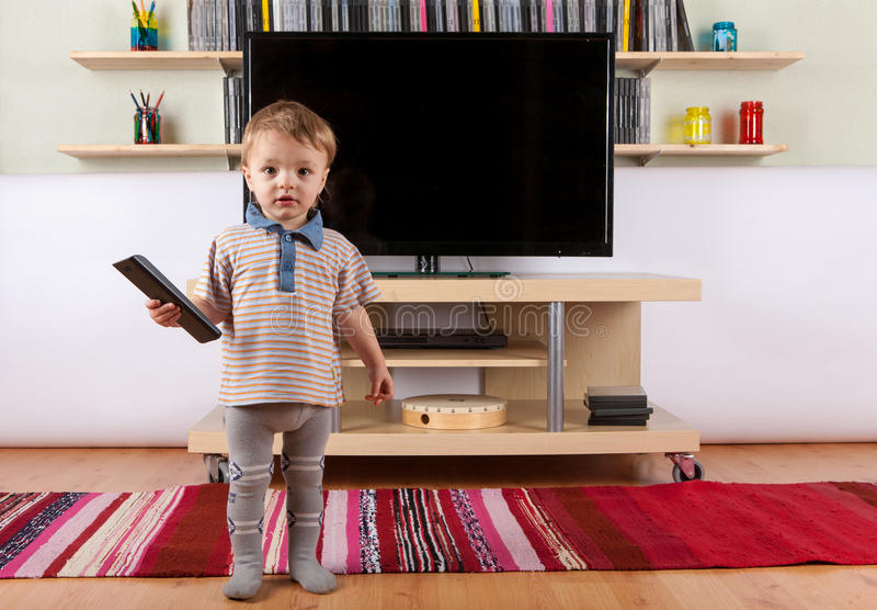 Cute baby boy with remote control in front of the TV royalty free stock photos