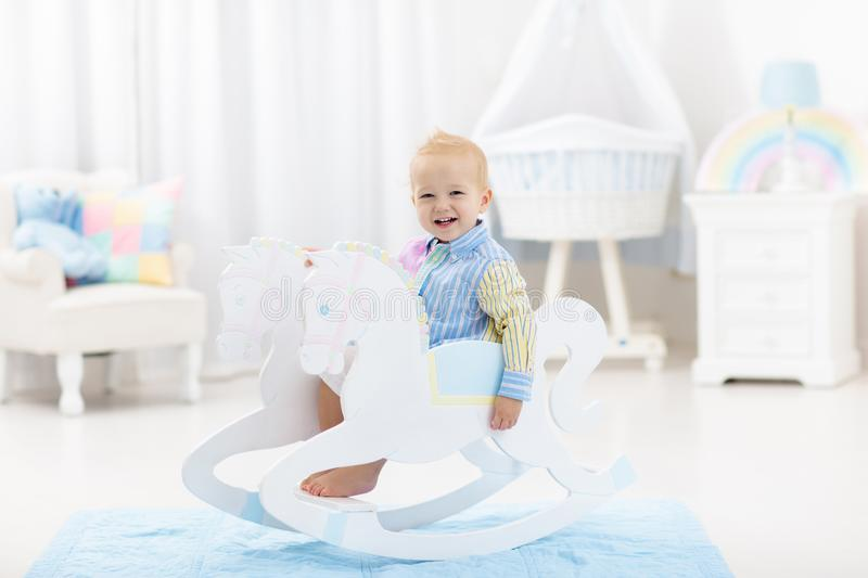 Baby boy in rocking horse toy. Cute baby boy riding wooden traditional rocking horse toy in white bedroom with pastel rainbow color decoration. Child playing in royalty free stock photography