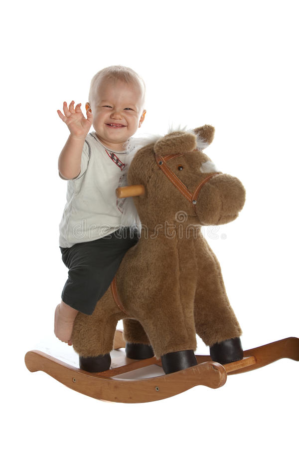 Cute Baby Boy On Rocking Horse Stock Images
