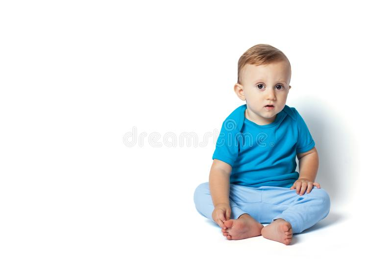 Cute baby boy sitting isolated on the white background. Copy place. Surprised and curious look of the baby will draw attention to information royalty free stock photos