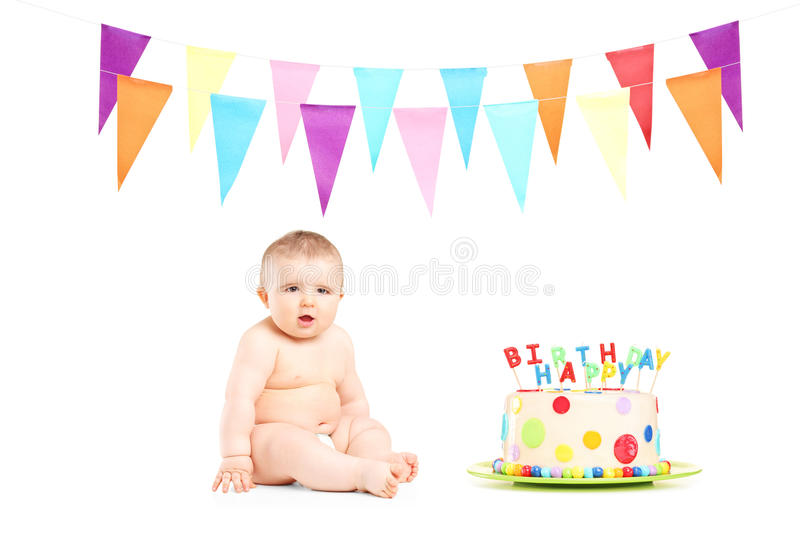 Cute baby boy sitting next to a birthday cake and party flags royalty free stock photo