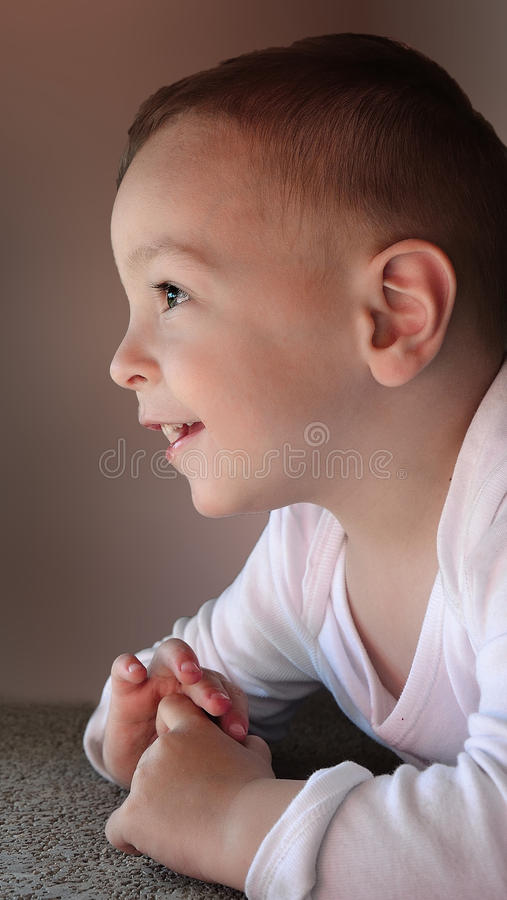 Cute baby boy smiling and looking up stock images